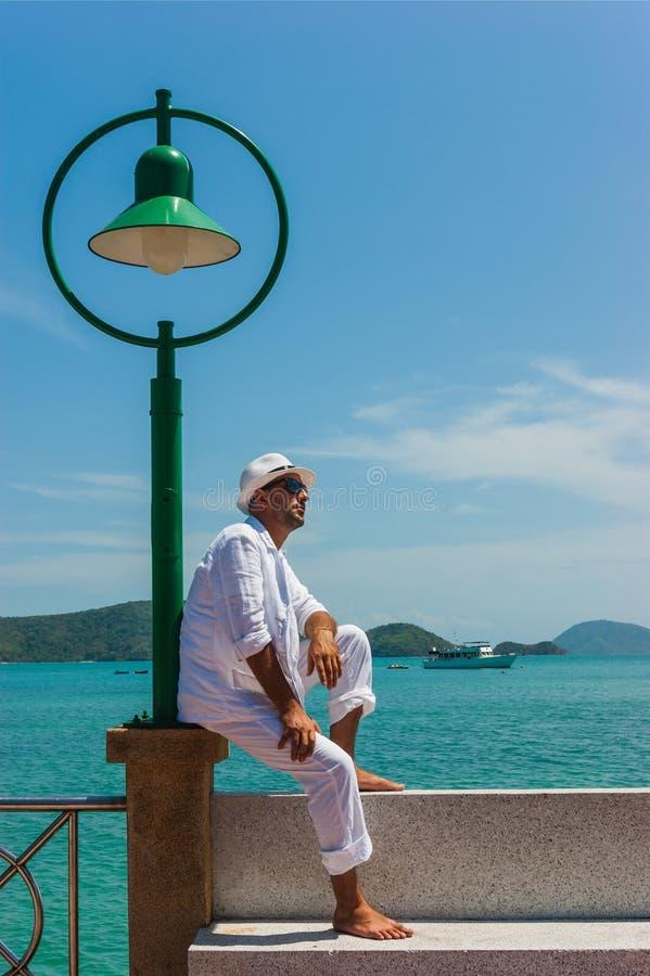 O homem em um terno e em um chapéu brancos que sentam-se em uma rocha nos vagabundos do mar fotos de stock royalty free