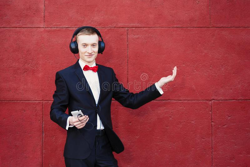 O homem em um terno está dançando O indivíduo novo está escutando a música em fones de ouvido grandes através do smartphone Conce foto de stock