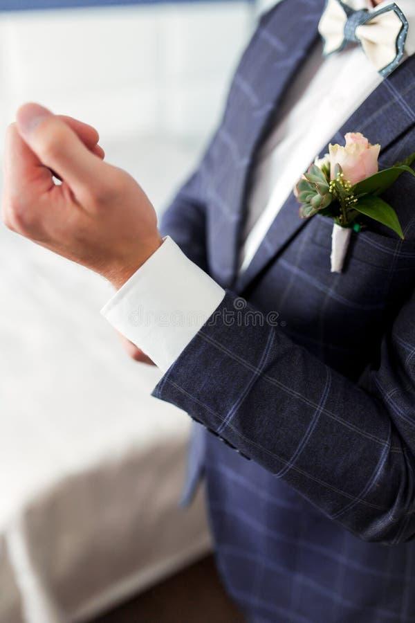 O homem em um terno prende a luva da camisa foto de stock