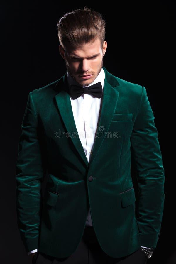 O homem em um terno verde de veludo está olhando para baixo imagens de stock