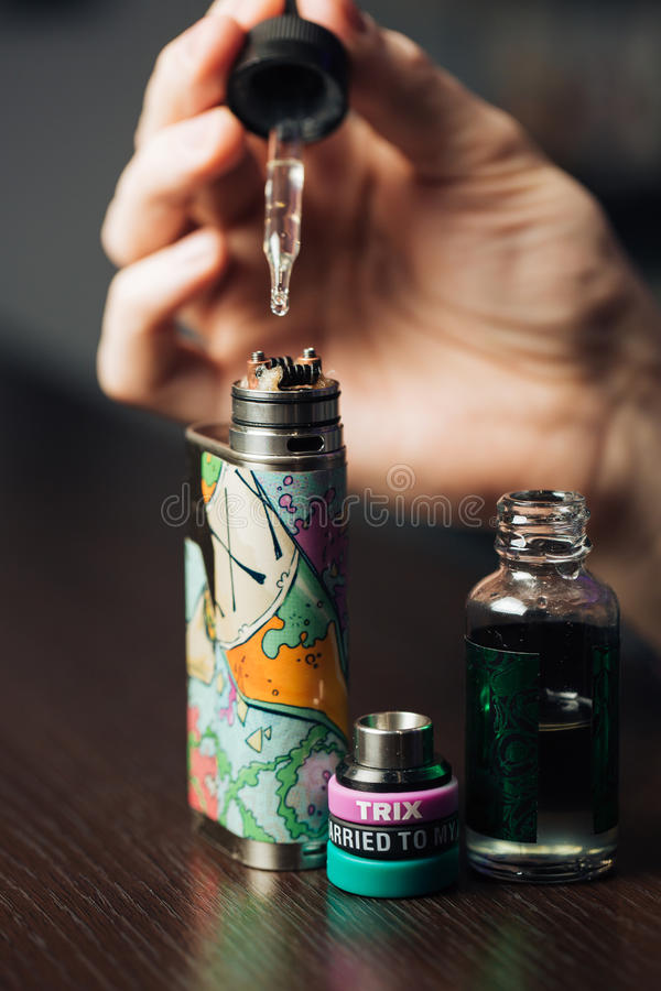 O homem em uma loja do vape está enchendo um líquido especial no e-cigarro imagem de stock