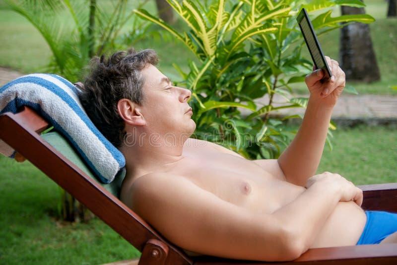 O homem em uma plataforma-cadeira está lendo em um EBook-leitor foto de stock