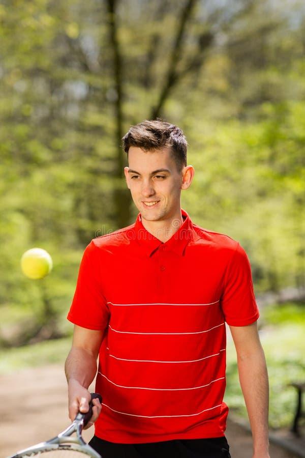 O homem em uma pose vermelha do t-shirt com uma raquete de t?nis e uma bola no fundo do parque verde Conceito do esporte fotos de stock