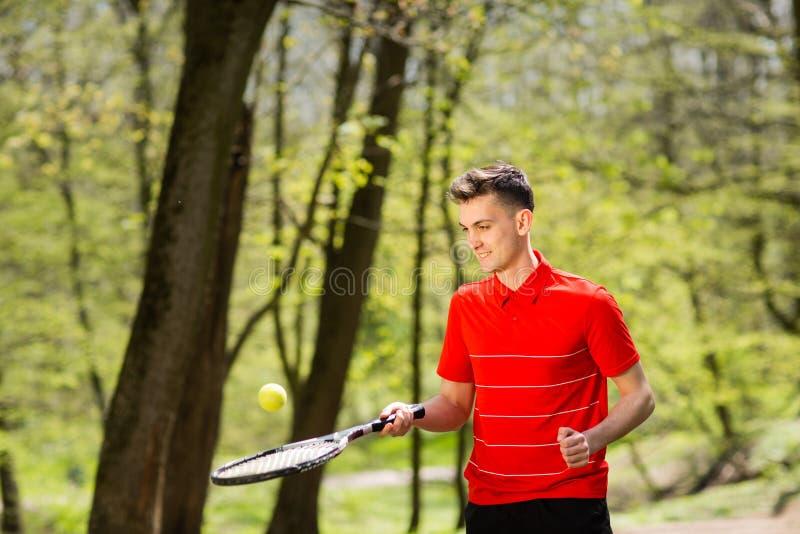 O homem em uma pose vermelha do t-shirt com uma raquete de t?nis e uma bola no fundo do parque verde Conceito do esporte foto de stock