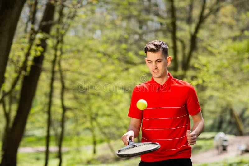 O homem em uma pose vermelha do t-shirt com uma raquete de t?nis e uma bola no fundo do parque verde Conceito do esporte imagem de stock