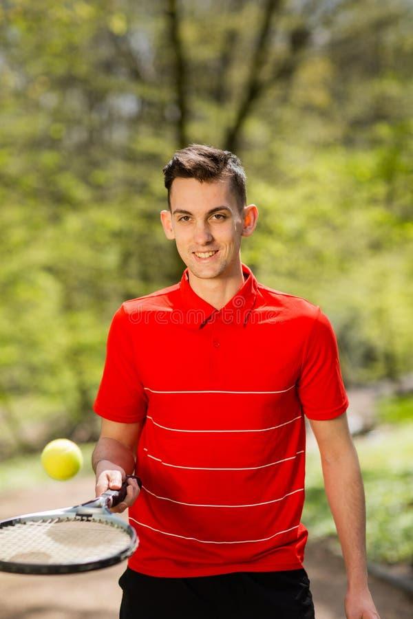 O homem em uma pose vermelha do t-shirt com uma raquete de t?nis e uma bola no fundo do parque verde Conceito do esporte fotografia de stock royalty free