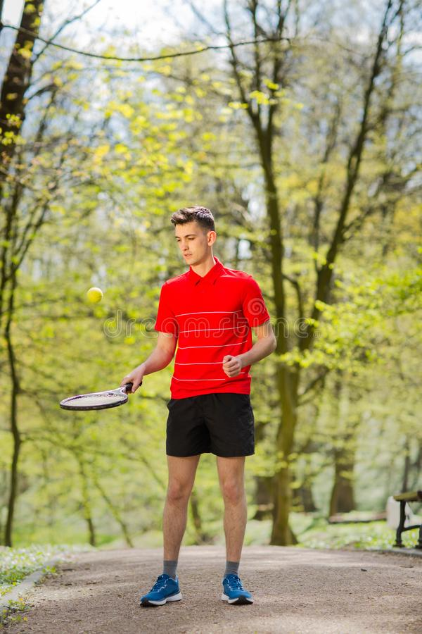 O homem em uma pose vermelha do t-shirt com uma raquete de t?nis e uma bola no fundo do parque verde Conceito do esporte imagens de stock royalty free
