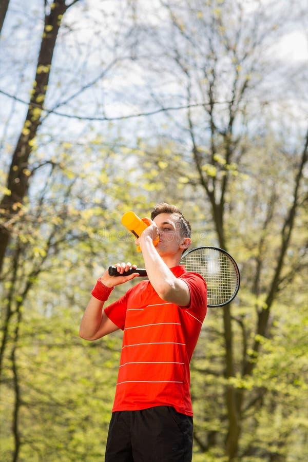 O homem em uma pose vermelha do t-shirt com uma raquete e uma ?gua pot?vel de t?nis de um par termoel?trico Conceito do esporte foto de stock royalty free