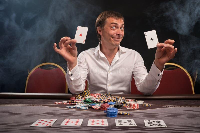 O homem emocional considerável está jogando o pôquer que senta-se na tabela no casino imagens de stock royalty free
