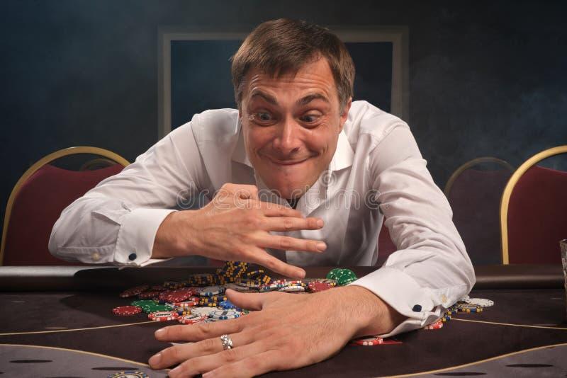 O homem emocional considerável está jogando o pôquer que senta-se na tabela no casino fotos de stock royalty free
