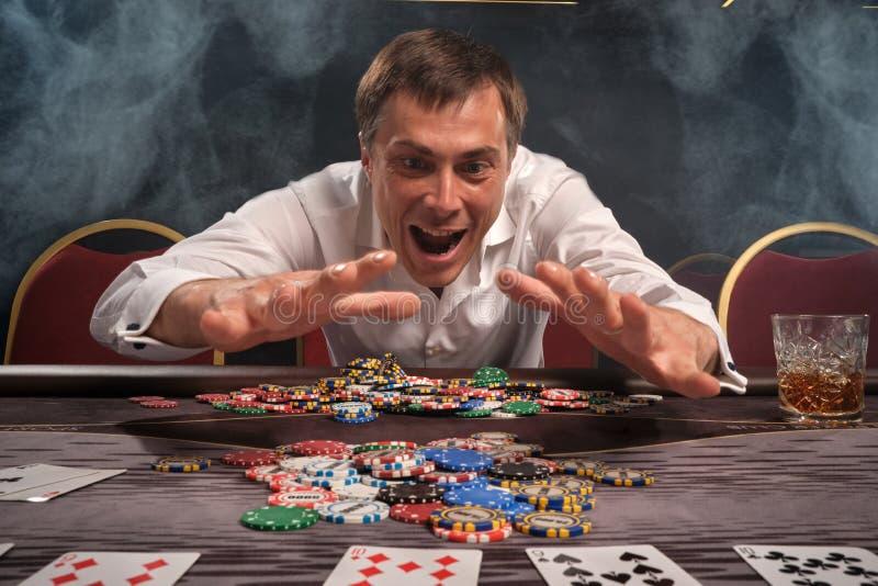 O homem emocional considerável está jogando o pôquer que senta-se na tabela no casino imagem de stock royalty free