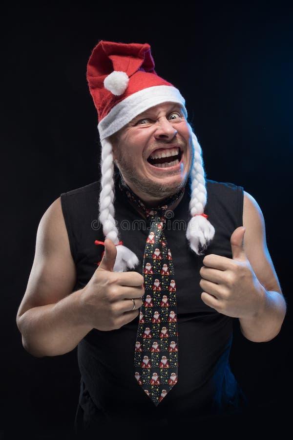 O homem emocional do ator cômico no tampão com tranças gesticula, em antecipação ao Natal e ao ano novo imagem de stock