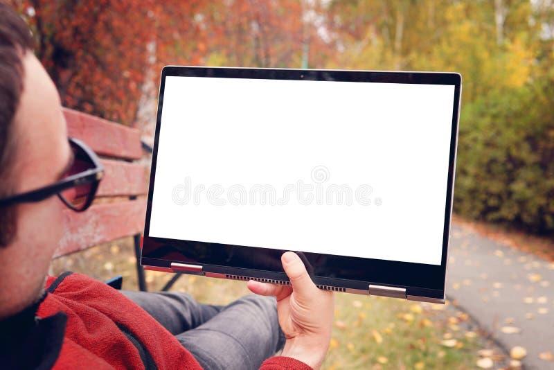 O homem encontra-se em um banco no parque do outono e olha-se a tela de um transformador moderno do ultrabook tela vazia para o p fotografia de stock royalty free