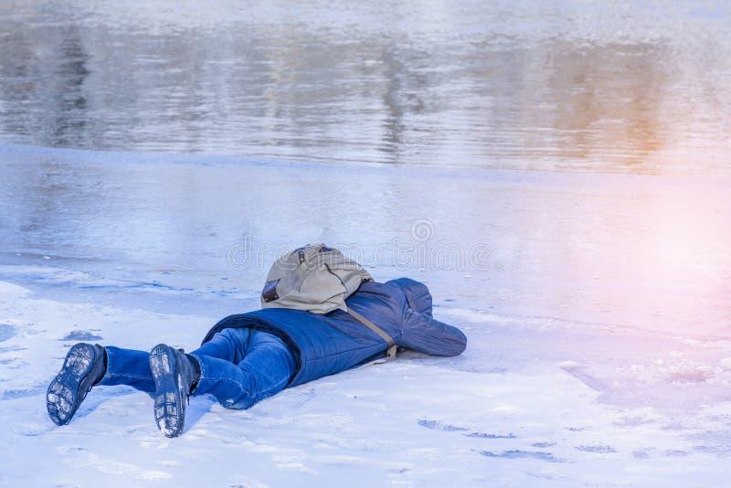 O homem encontra-se no gelo no inverno, um homem encontra-se no gelo do rio e dos olhares do inverno através do gelo no cancelado fotos de stock