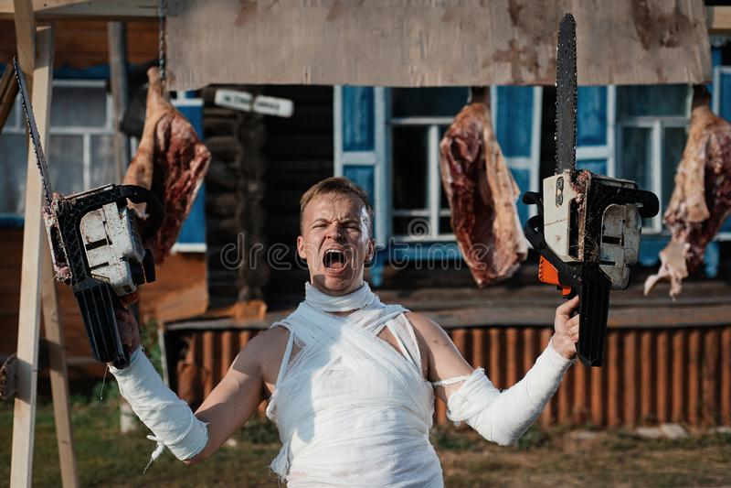 O homem enfaixado grita terrivelmente, guardando duas serras de cadeia em suas mãos no fundo de carcaças de porco fotografia de stock royalty free