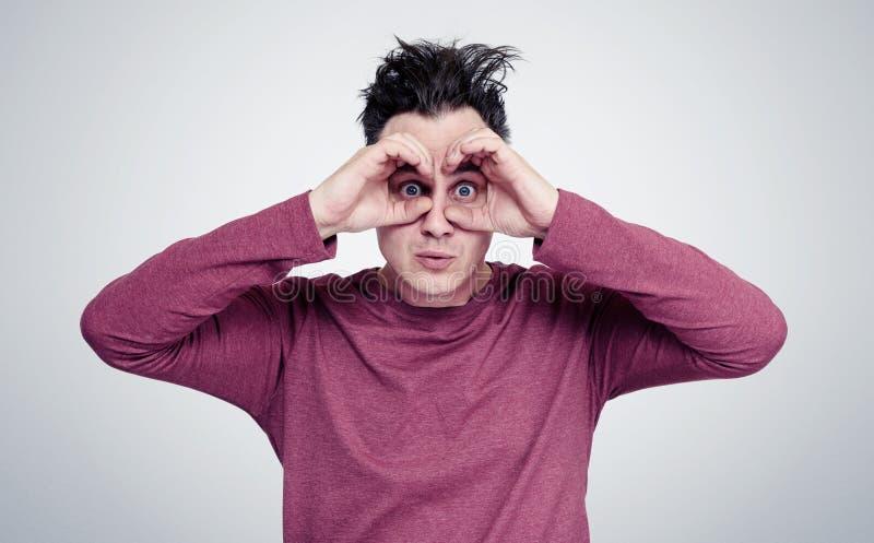 O homem engraçado faz os binóculos em torno dos olhos das mãos imagens de stock royalty free