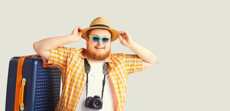 O homem engra?ado gordo um sorriso da mala de viagem vai em um fundo cinzento imagem de stock royalty free