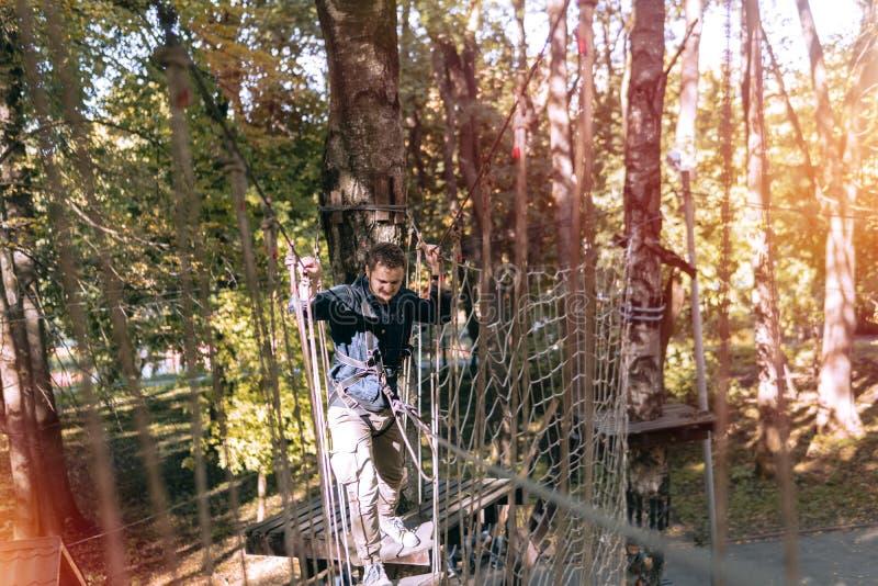 O homem, engrenagem de escalada em um parque da aventura é contratado em obstáculos da escalada ou da passagem na estrada da cord fotos de stock royalty free