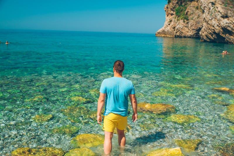 O homem entra para cancelar a água do mar por joelhos Vista bonita imagem de stock