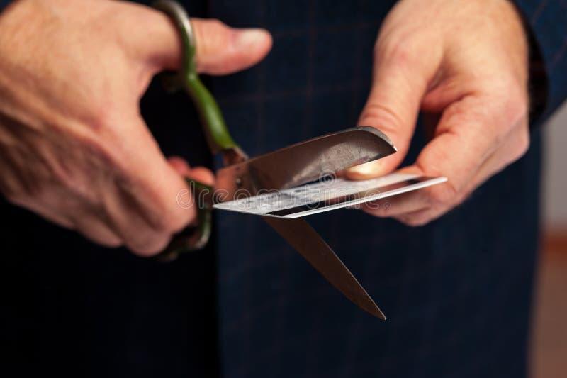 O homem entrega as tesouras do wirh que cortam o cartão de crédito bancário foto de stock royalty free