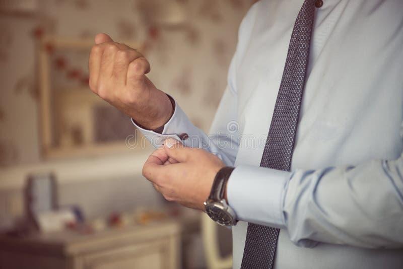 O homem entrega botão de punho de prata à moda de fixação nas luvas azuis dos punhos da camisa no terno formal fotografia de stock royalty free