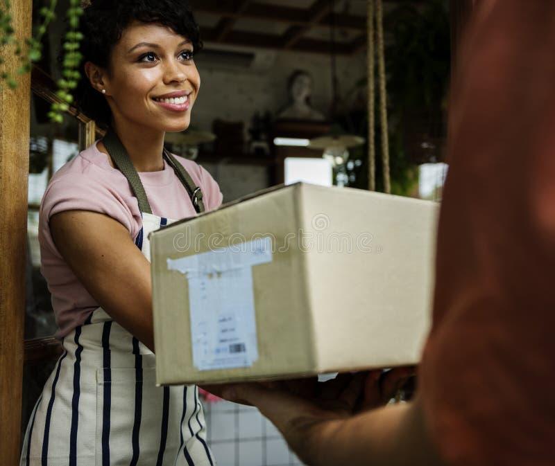 O homem entrega a caixa postal à mulher na frente da parada fotos de stock royalty free