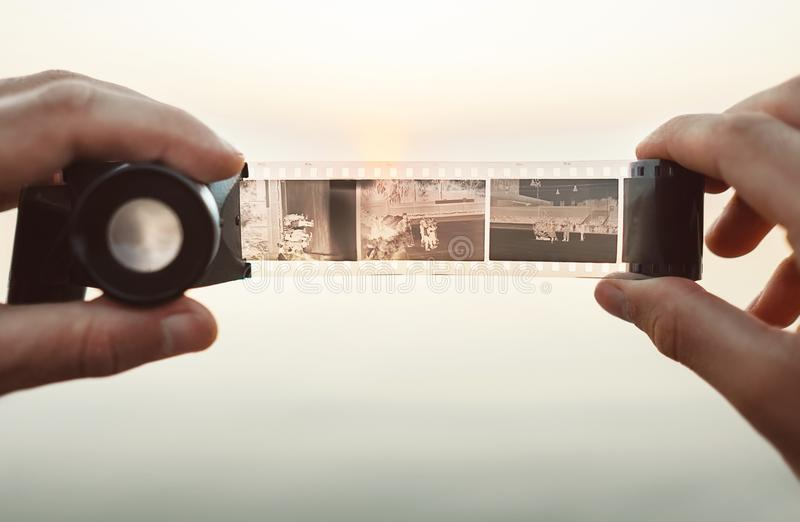 O homem entrega a imagem usando o visor velho do negativo de filme do vintage 35mm para ver quadros no fundo do por do sol imagens de stock