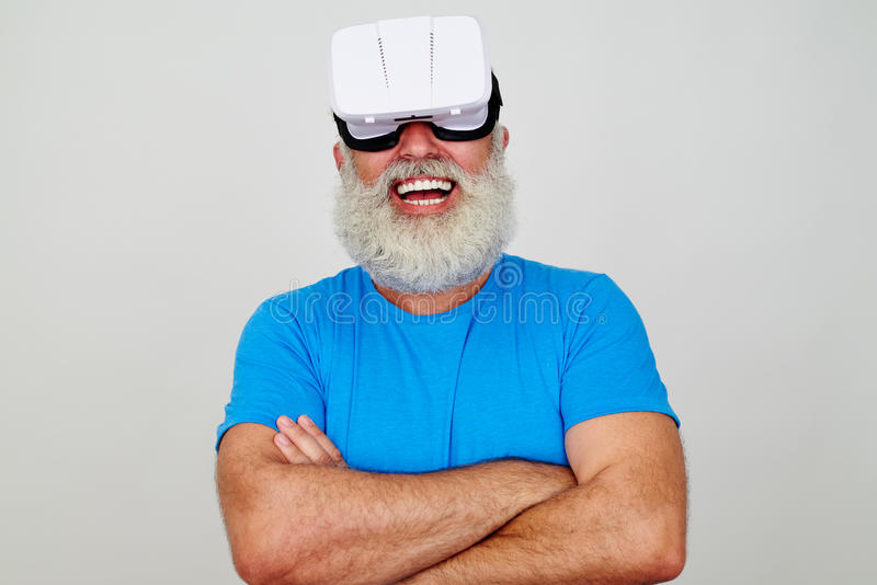 O homem envelhecido de sorriso com os braços cruzados que vestem a realidade virtual dirige foto de stock royalty free