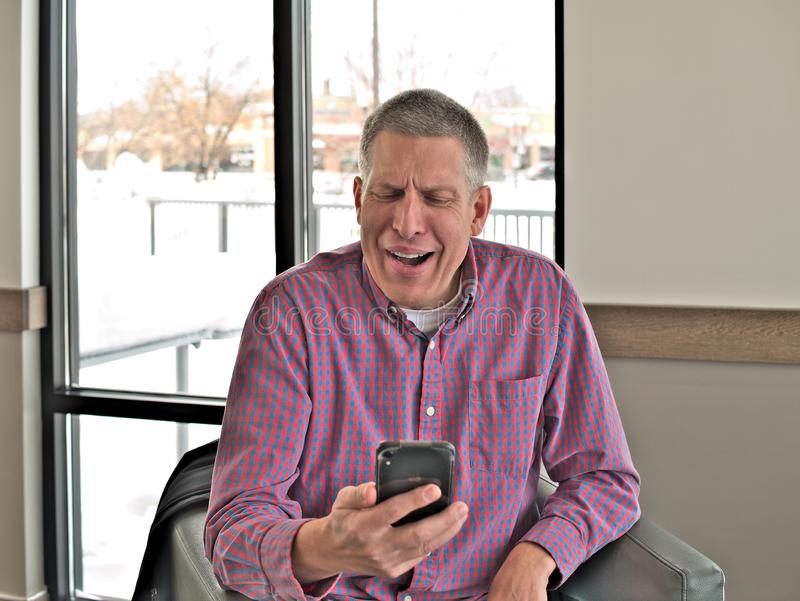 O homem envelhecido médio considerável na roupa ocasional expressa a resposta emocional a uma mensagem em seu telefone celular mó fotos de stock