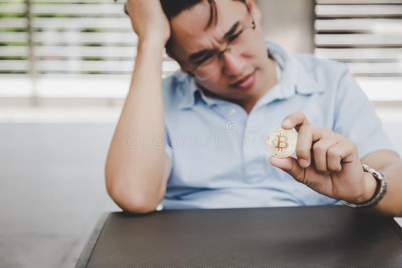 O homem envelhecido meio do acionista está guardando o bitcoin e está olhando-o Ele imagem de stock
