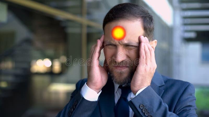 O homem envelhecido meio sofre da dor de cabeça, ponto indica a dor da enxaqueca, close up imagem de stock royalty free