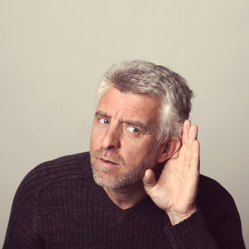 O homem envelhecido surdo escuta fotos de stock royalty free