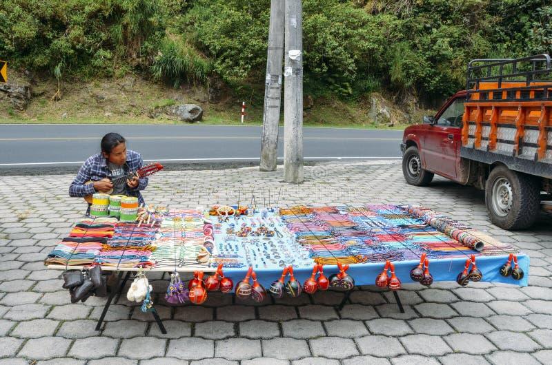 O homem equatoriano nativo local joga o banjo ao vender artesanatos locais no lado da estrada fotografia de stock royalty free