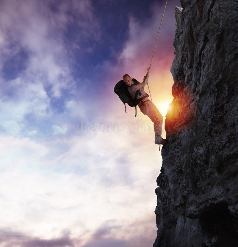 O homem escala uma montanha alta do perigo com uma corda durante o por do sol fotografia de stock royalty free