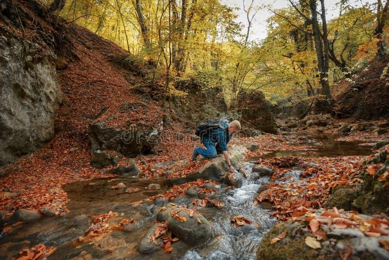 O homem escava acima a água de um córrego da montanha foto de stock royalty free
