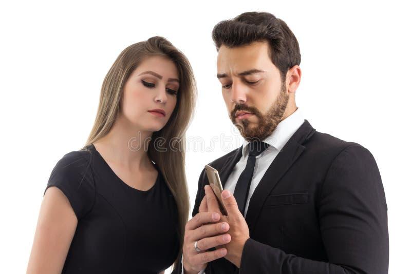 O homem esconde a tela do telefone celular curioso do ` s da mulher Os dois fotografia de stock royalty free