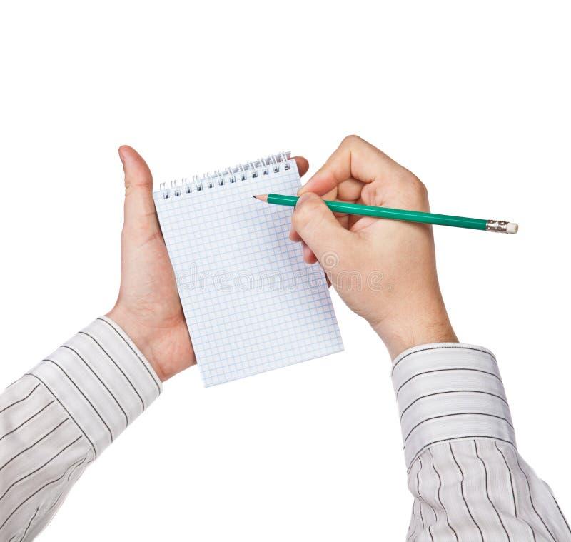 O homem escreve em um caderno imagens de stock