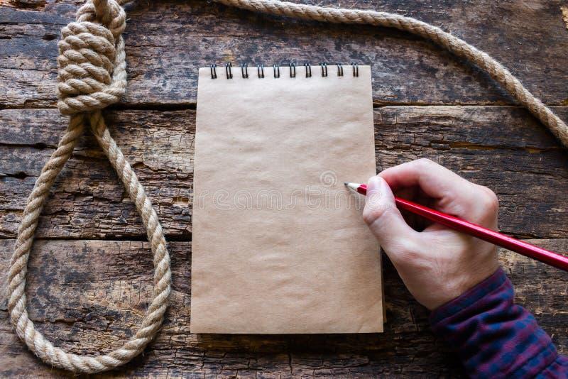 O homem escreve uma nota de suicídio imagens de stock