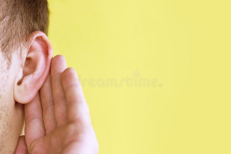 O homem escuta atentamente com sua palma sua orelha, fim acima no fundo amarelo, conceito da notícia imagem de stock royalty free