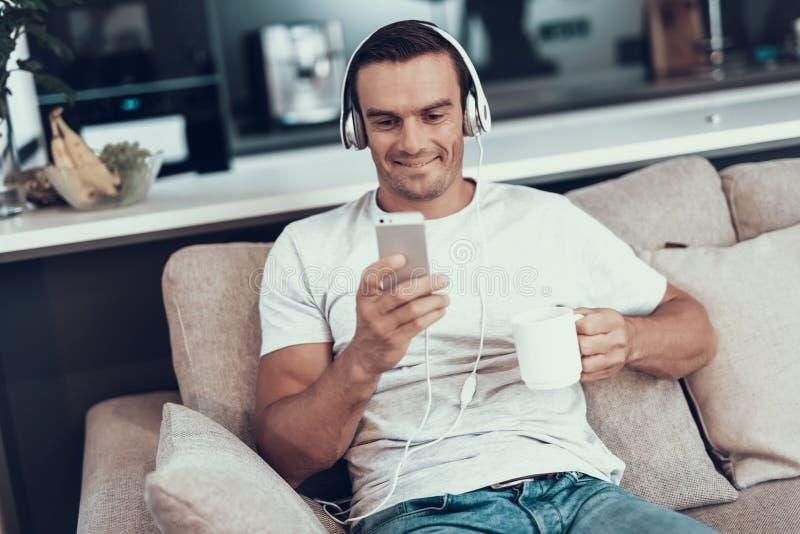 O homem escuta a música nos fones de ouvido e bebe o chá fotografia de stock royalty free