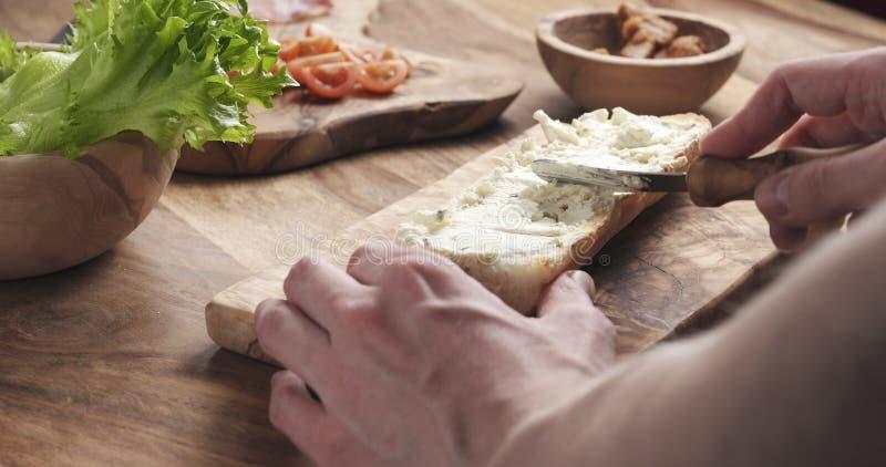 O homem espalhou o queijo creme com as ervas sobre o baguette no movimento lento fotografia de stock