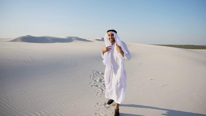 O homem esplêndido do xeique dos UAE do Arabian olha duramente na distância e na lagoa imagem de stock
