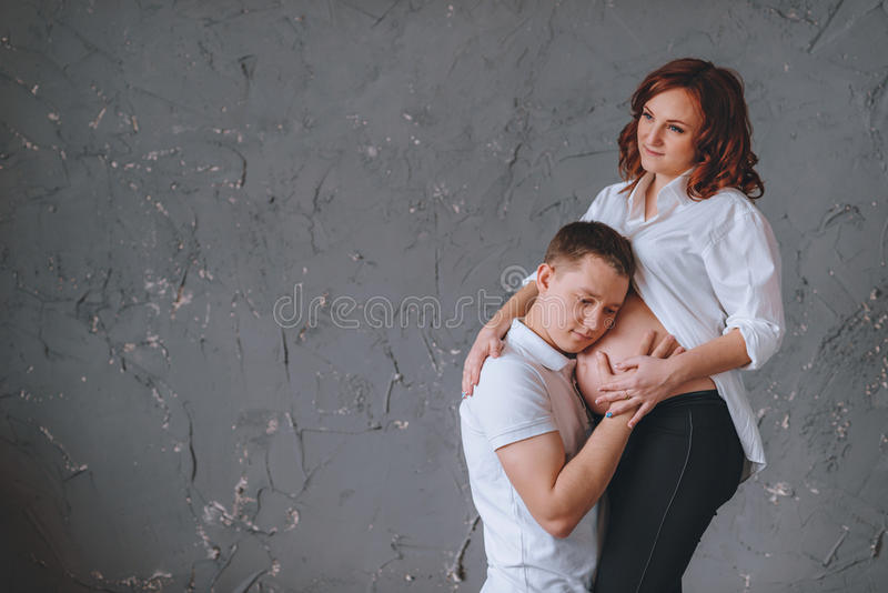 O homem está abraçando o estômago de uma mulher gravida Há um lugar para Tex em um fundo cinzento Olha afastado imagem de stock