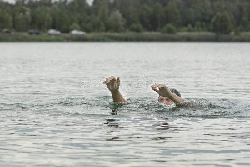 O homem está afogando-se no lago foto de stock