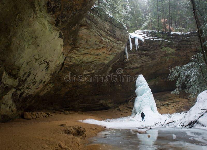 O homem está ao lado do monte gigante do gelo em Ash Cave imagem de stock