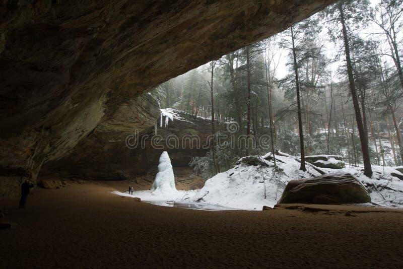O homem está ao lado do monte gigante do gelo em Ash Cave fotos de stock royalty free