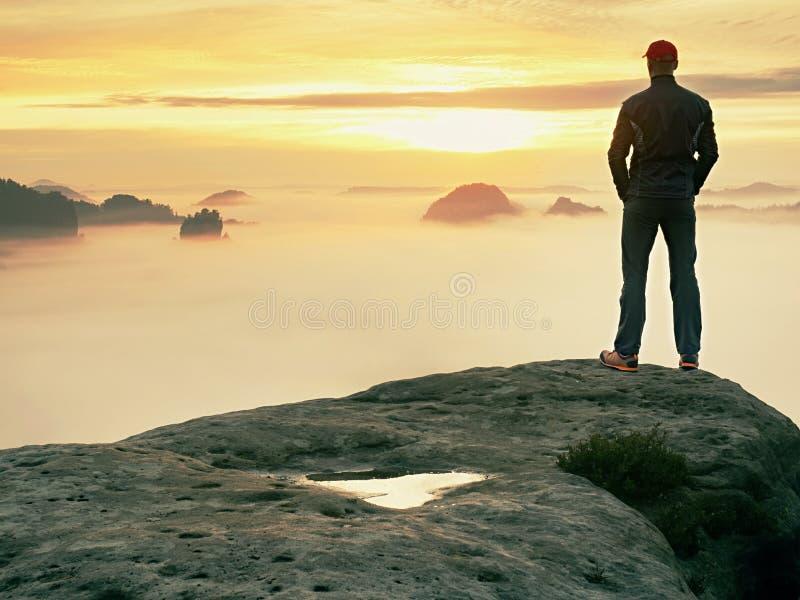 O homem está apenas no pico da rocha Caminhante que olha ao outono Sun no horizonte Momento bonito o milagre da natureza imagem de stock