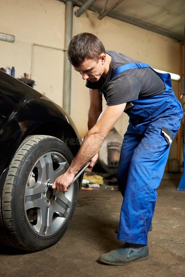 O homem está apertando os parafusos em um pneu fotos de stock royalty free
