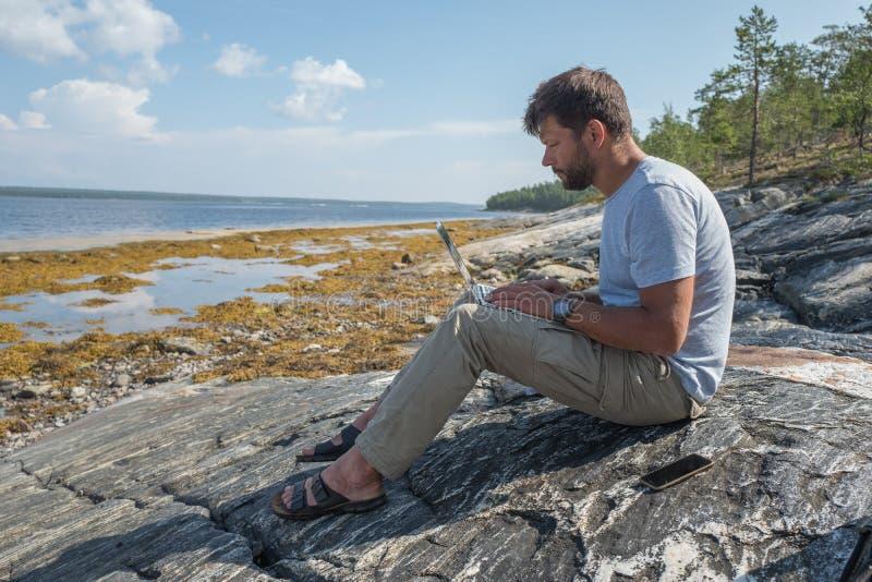 o homem está assentando na pedra próximo do mar e está trabalhando com portátil fotografia de stock