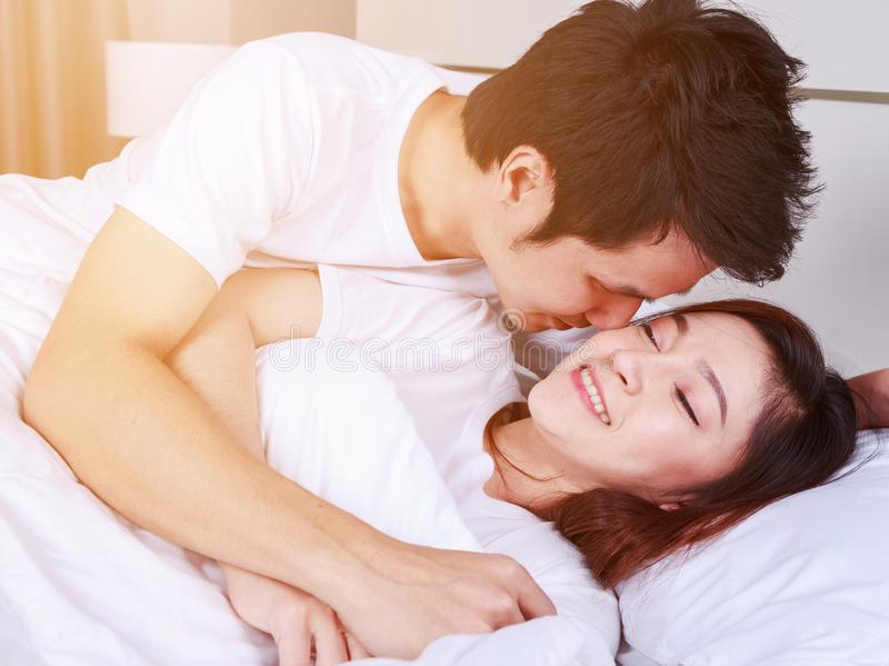 O homem está beijando sua esposa de sorriso bonita no mordente na cama fotografia de stock